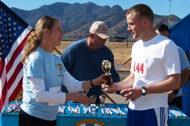 Lt. Col. Laura Knapp, 309th Military Intelligence Battalion commander, awards Robert Finicum with the first place overall male trophy following the 2nd 309th Military Intelligence Battalion Sentinel Pursuit 8K Run Saturday on Hunt Road. Finicum finished with a time of 26:26. The top three overall winners received a trophy. The top three finishers in each age category received a medal.
