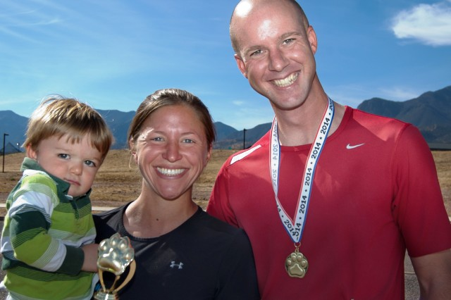 "The Bosarge Family displays their awards after Saturday�'s run on Fort Huachuca. Jonathan Bosarge placed 3rd in the 30 �"" 39 male category with a time of 34:14. Jennifer Bosarge placed first overall female, completing the race in 33:07. Jonathan pushed their son, Adam, 2, in a running stroller while Jennifer set a blistering pace."