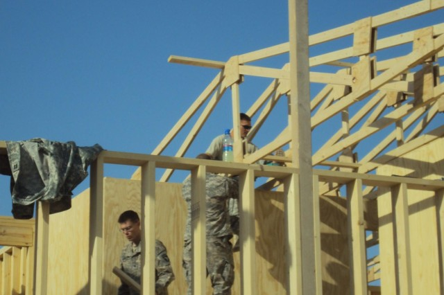 "Soldiers with the 6th General Support Aviation Battalion, 101st Aviation Regiment, build the second floor of the future ""First Cup"" coffee house during their deployment to Kandahar Airfield, Afghanistan in 2010. (U.S. Army photo/released)"