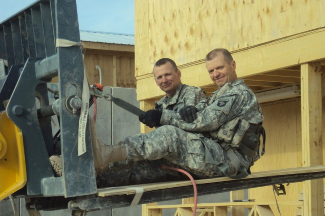 "Chaplain Kevin Trimble (right) and Lt. Col. T. Bradley Ninness with 6th General Support Aviation Battalion, 101st Aviation Regiment, prepare to hang the original ""First Cup"" coffee house sign following the completion of the building at Kandahar Airfield, Afghanistan in 2010. (U.S. Army photo/released)"