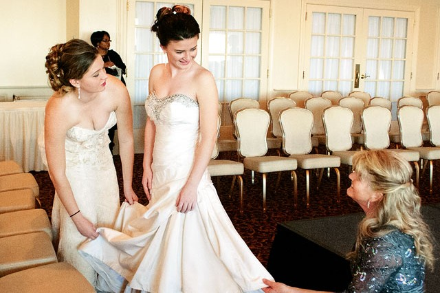 Kylee Shoop, left, 18, and mother Bobbi, fluff the dress of Kalyn, middle, 16, during the Annual Bridal Fair at the Officers' Club Saturday. Kylee and Kalyn were models during a fashion show that showcased wedding gowns, cocktail dresses and evening wear.