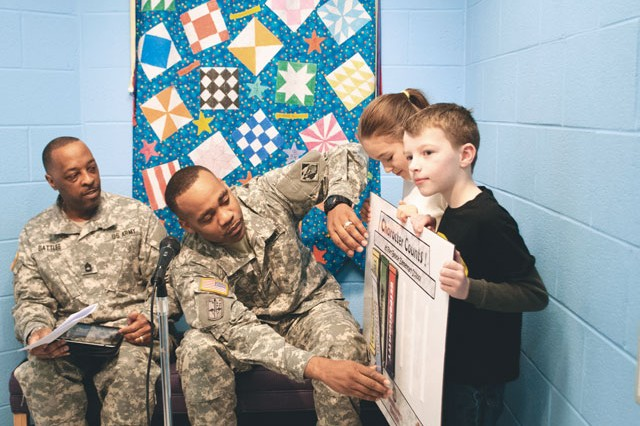 "Sgt. 1st Class Michael Battles, left, of the Staff Judge Advocate Office watches Sgt. Erick Harris, also of the SJA office, pin the tenet ""Fairness"" to the ""Character Counts"" board held by Jasmine Padilla, 9, and John Copeland, 9, at Fort Belvoir Elementary School Feb. 20."