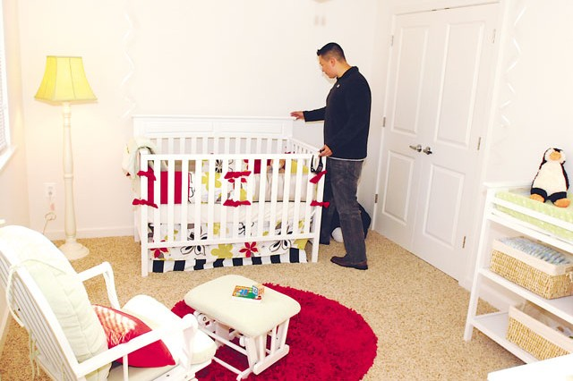 Petty Officer 1st Class Sergio Rivassorto, Marine Barracks Washington, D.C., looks at a bedroom during a tour of the Dogue Creek Village development. He was looking at the renovations during an open house in November 2013.
