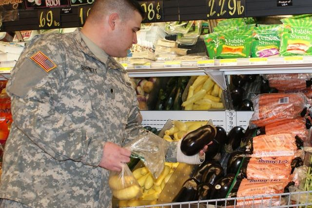 Spc. Logan Burnett picks out eggplant during a recent shopping trip at Fort Hood's Clear Creek Commissary.