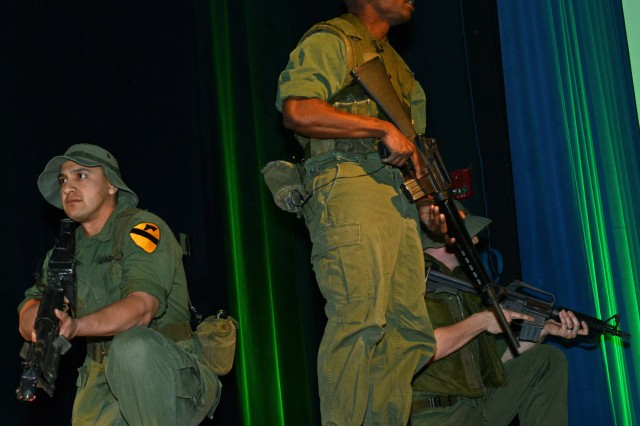 """Soldiers of """"The Old Guard,"""" based in Joint Base Myer-Henderson Hall, Va., perform a short Vietnam re-enactment prior to FedEx CEO Fred Smith's remarks. The Soldiers are wearing Vietnam-era uniforms conducting night operations."""