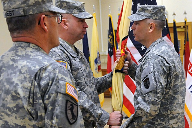 Col. Vincent Barker, outgoing ASC-ARE commander, passes the unit colors to Brig. Gen. Phillip Jolly, commander of Army Reserve Sustainment Command, during a change of command ceremony in Heritage Hall at Rock Island Arsenal, Ill., March 1. (Photo by Sgt. 1st Class Shannon Wright, ASC Public Affairs Office)