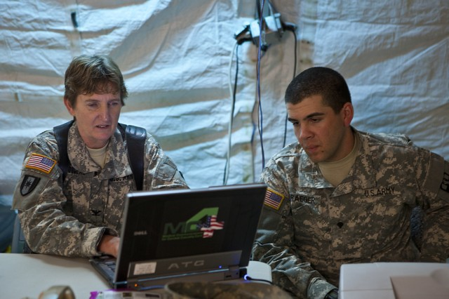 Col. Rebecca Douglas, chief nurse of the 115th Combat Support Hospital and Spc. Bryan Draeger, a signal officer, verify that notional patient information is flowing through the Army's MC4 electronic medical record system during a mass casualty exercise in Louisiana.