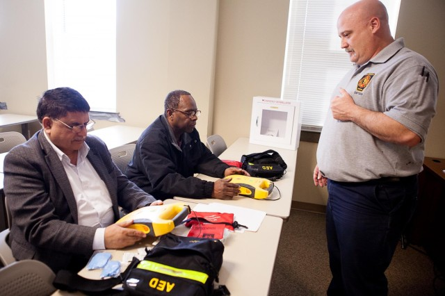 Abdul Qayyum, Bowling Center facility manager, left, and LeRoy Harris, Community Center facility manager, take part in a class on automated external defibrillators taught by Joint Base Myer-Henderson Hall fire department Capt. James Angerett, right, in Building 417 Feb. 24, 2014. Some buildings already have defibrillators installed; more will be installed soon.