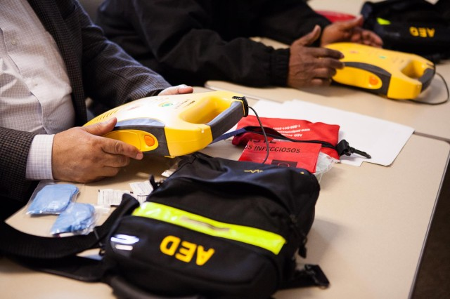 Abdul Qayyum, Bowling Center facility manager, left, and LeRoy Harris, Community Center facility manager, take part in a class on automated external defibrillators taught by Joint Base Myer-Henderson Hall fire department Capt. James Angerett (not pictured) in Building 417 Feb. 24, 2014. Some buildings already have defibrillators installed; more will be installed soon.