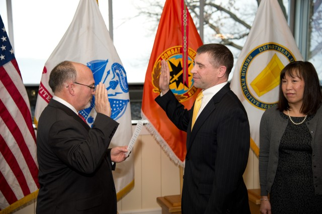 Gary Martin, deputy to the commanding general, U.S. Army Communications-Electronics Command, administers the Senior Executive Service oath of office to Larry Muzzelo, director of the CECOM Software Engineering Center marking him as a new member of the Senior Executive Service, during his promotion ceremony February 25 at the Top of the Bay at Aberdeen Proving Ground, Md. His promotion was effective Jan. 12.
