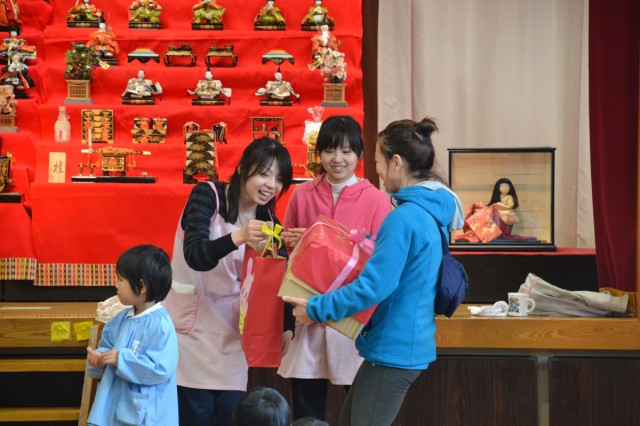 Hosen Kindergarten staff present Sagamihara Family Housing Area Miho Onda, youth program instructor, with parting gifts of snacks and paper hina dolls during a visit to the school March 3 to celebrate Friendship Day.  (U.S. Army photos by Candateshia Pafford)