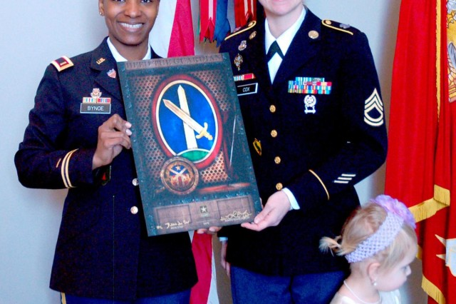 Second Lt. Lisa Bynoe, Army Reserve officer at Fort Totten, N.Y., and government civilian with JBM-HH Trial Defense Services, and Sgt. 1st Class Bobbie Cox, human resources specialist at U.S. Army Physical Disability Agency, Crystal City, Va., (right), pose for a photograph following Cox's re-enlistment of indefinite status Feb. 28 at the Women in Service for America Memorial. Cox's daughter, Haleigh, 3, stood with her during the re-enlistment ceremony.