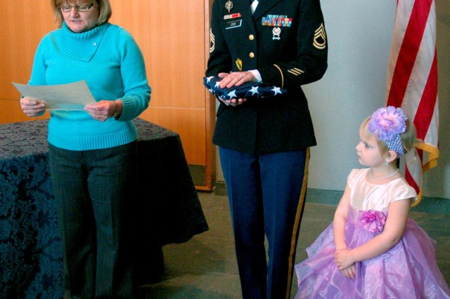 Jan Fitzsimmons, Women in Military Service for America Memorial deputy director, presents Sgt. 1st Class Bobbie Cox with an American flag which was unfurled at the Women's Memorial prior to her re-enlistment there, Feb. 28. Cox's daughter, Haleigh, 3, stands with her mother.