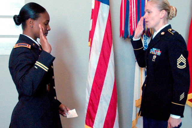 Second Lt. Lisa Bynoe, Army Reserve officer at Fort Totten, N.Y., and government civilian with JBM-HH Trial Defense Services, administers the oath of re-enlistment to Sgt. 1st Class Bobbie Cox (right), Feb. 28 at the Women in Service for America Memorial. Cox, a human resources specialist at the U.S. Army Physical Disability Agency, Crystal City, Va., re-enlisted in an indefinite status pledging the remainder of her military career to serve the Army.