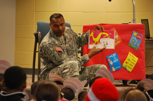 """Col. Jerry Jones, Expeditionary Contracting Command chief of staff, pauses while reading Dr. Suess' """"The Foot Book,"""" to show a graphic to Kindergarteners at the Morris Elementary School March 3 as part of the National Read Across America Day."""
