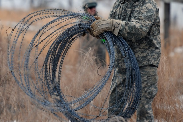 Pfc. David Baillargeon, a wheeled vehicle mechanic with 642nd Engineer Company, gathers a coil of old concertina wire at Rappahannock Camp at Fort A.P. Hill, Va.