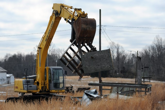 After he knocked down the old guard tower, Spc. Zach Stiglitz took it apart with the excavator and dropped the scrap into a dumpster.