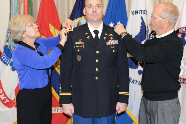 Newly promoted Lt. Col. Daniel M. Woodlock's parents place their son's new rank insignia on his uniform during his promotion ceremony held at Fort Lesley J. McNair, March 4, 2014.   Woodlock is the  Joint Force Headquarters - National Capital Region and the U.S. Army Military District of Washington Medical Plans and Operations Officer since August 2013.