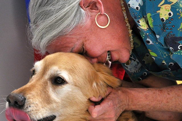 Optometric Technician Pat McLaughlin snuggles with Human Animal Bond member Ruie Gibson's dog Titan during a visit Feb. 27 at Munson Army Health Center, Fort Leavenworth, Kan. HAB teams, comprised of dogs with their handlers and occasionally cats and rabbits with their handlers, visit area hospitals, nursing homes, schools and libraries providing pet therapy. The visits to MAHC give staff a break from stress, and many employees said they look forward to the visits.
