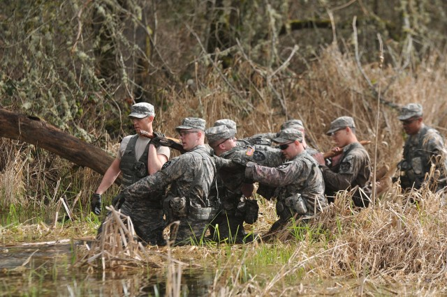 Soldiers with 2nd Squadron, 1st Cavalry Regiment, 4-2 Stryker Brigade Combat Team, 7th Infantry Division, carry a mock litter patient through water March 5 during a Spur Ride on Joint Base Lewis-McChord, Wash. (U.S. Army photo by Sgt. Kimberly Hackbarth, 4-2 SBCT, 7th Inf. Div. Public Affairs Office)