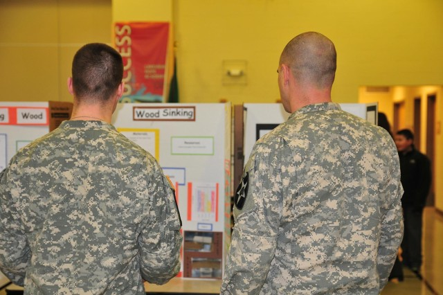 Soldiers with 4-2 Stryker Brigade Combat Team, 7th Infantry Division judge a science fair project Feb. 20 at Lakeview Hope Academy in Lakewood, Wash. (U.S. Army photo by Sgt. Kimberly Hackbarth, 4th SBCT, 2nd Inf. Div. Public Affairs Office)