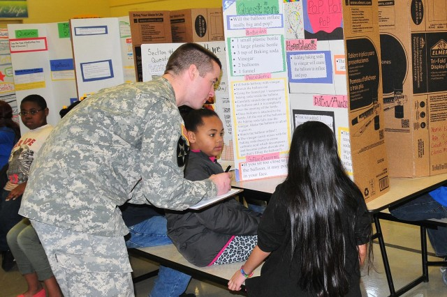 Sgt. James Roeser, an intelligence analyst with 2nd Squadron, 1st Cavalry Regiment, 4-2 Stryker Brigade Combat Team, 7th Infantry Division, judges a science fair project Feb. 20 at Lakeview Hope Academy in Lakewood, Wash. (U.S. Army photo by Sgt. Kimberly Hackbarth, 4th SBCT, 2nd Inf. Div. Public Affairs Office)