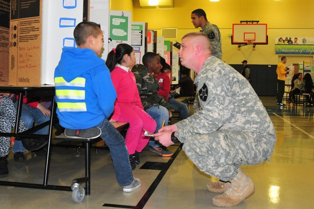 Sgt. Michael Helms (foreground), and Spc. Tyneil Rankin, both with 2nd Squadron, 1st Cavalry Regiment, 4-2 Stryker Brigade Combat Team, 7th Infantry Division, judge science fair projects Feb. 20 at Lakeview Hope Academy in Lakewood, Wash. (U.S. Army photo by Sgt. Kimberly Hackbarth, 4th SBCT, 2nd Inf. Div. Public Affairs Office)