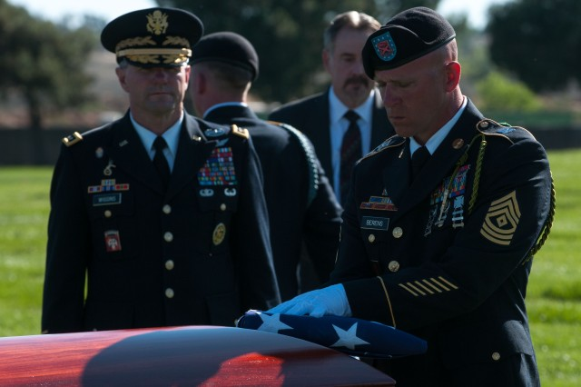 First Sgt. Matthew Berens, 1st Battalion, 18th Infantry Regiment, 2nd Armored Brigade Combat Team, 1st Infantry Division, holds a folded American flag to the casket of Walter D. Ehlers during a March 8, 2014, memorial service at the Riverside National Cemetery in Riverside, Calif.