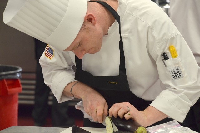 Sgt. Gabriel Earle, Fort Gordon, thinly slices eggplant for eggplant chips during the Armed Forces Chef of the Year event. The event kicked off the 39th Annual Military Culinary Arts Competitive Training Event, March 9, 2014, at Fort Lee, Va.