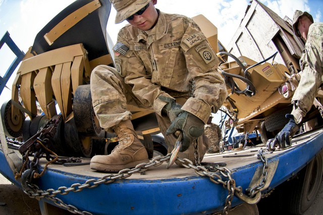 Spc. Alexander Istenes, a truck driver with the 82nd Airborne Division's 1st Brigade Combat Team, tightens a chain holding military equipment on the truck of a local national before the return leg of a logistics resupply convoy, July 9, 2012, in Ghazni Province, Afghanistan.