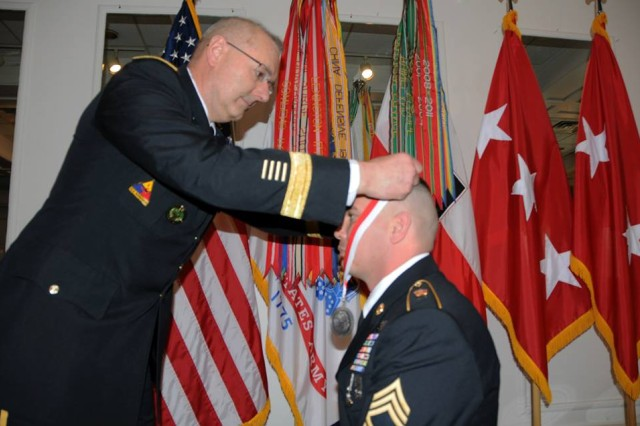 Lt. Gen. Michael S. Tucker, First Army commanding general, drapes an Honorable Order of Saint George Silver Medallion around the neck of Sgt. 1st Class Scott D. Smith during a knighthood ceremony at Rock Island Arsenal, Ill., Feb. 28. Induction into the Order recognizes a long and distinguished career by a member of the United States Armor Association. The association named its award in honor of Saint George, the patron saint of mounted warriors. Smith, who served several years as an Armor Soldier, is currently stationed at First Army Headquarters at Rock Island Arsenal and serves as Tucker's transportation management coordinator and administrative assistant to the First Army command sergeant major.