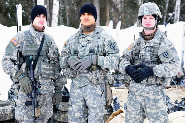 Spc. Michael Hall (L), Spc. Steven Cuadros(C) and Spc. Jordan Kurdziel (R), Arctic tough Soldiers assigned to 5th Squadron, 1st Cavalry Regiment,  1st Stryker Brigade Combat Team, 25th Infantry Division, pose for a photo prior to setting up the new digs, which they will call home during the U.S. Army Alaska Winter Games at Fort Wainwright, Alaska. The games will test the Soldiers and the units�' ability to execute required cold weather skills and tasks and build esprit de corps with tough, demanding and realistic training. There are 29 teams, each team is comprised of ten Soldiers. The teams are competing in seven different events March 10-13.  March 10, 2014. Fort Wainwright, Alaska. (Photo by Capt. Patrick Sawicki U.S. Army Alaska public affairs)