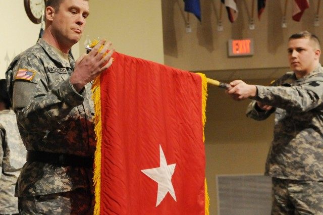 """Brig. Gen. R. Andrew Bassford, deputy commanding general of the 88th Regional Support Command, unfurls his one-star flag, which was presented during his promotion ceremony at the 88th RSC headquarters at Fort McCoy, Wis., Feb. 21, 2014. """"I'm honored, and I hope to prove worthy of the honor,"""" said Bassford. """"But at the end of the day, this promotion just means that the Army has given me a little more leverage to do the things that actually matter - accomplish the mission and take care of soldiers."""""""