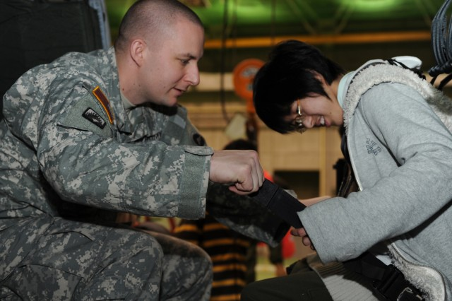 Staff Sgt. John Staudacher, assigned to the U.S. Army Aviation Battalion Japan at Camp Zama, Japan, helps a 10th-grader at the Zama Special Needs School secure her seatbelt while seated inside a helicopter. Four students from the school toured Camp Zama Feb. 7 and got to meet with several personnel who work on the installation and learn more about their diverse missions.