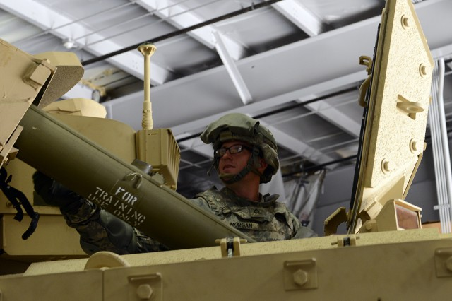 Pfc. Jacob Morgan loads a TOW missile launcher on a Bradley Fighting Vehicle during the Army's Physical Demands Study, at Fort Stewart, Ga., March 12, 2014.
