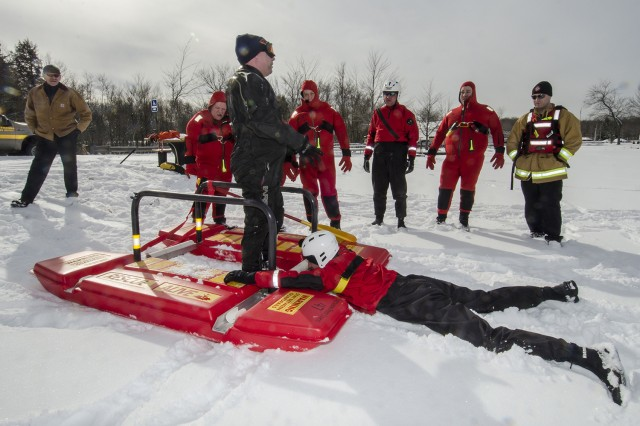 Keith DiPatri tells fellow firefighters how to use a rescue platform during ice rescue training at Tobyhanna Army Depot. Firefighters broke through ice 11 inches thick to conduct their annual ice rescue training on Barney's Lake here. As part of the training, each firefighter demonstrates how to pull themselves from the water using only a small ice pick. Playing the role of victim or rescuer, the firefighters also perform rescues using a rescue platform, rescue sled or just a rope to remove the victim. Tobyhanna Army Depot has its own Dive Team/Water Rescue Team and assists local fire departments in fire fighting and search and rescue.
