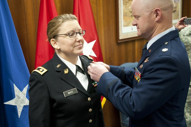 Air Force Lt. Col. Jamie White pins new insignia to the uniform of his wife, Army Maj. Angela White, during an appointment ceremony in Frankfort, Ky., Feb. 21, 2014. Maj. White is the first female chaplain with the Kentucky Guard in 25 years. (U.S. Army National Guard photo by Staff Sgt. Scott Raymond)