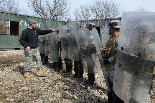 Sgt. 1st Class Daniel Konrardy, INIWIC instructor, shows students proper alignment and positioning of riot shields.
