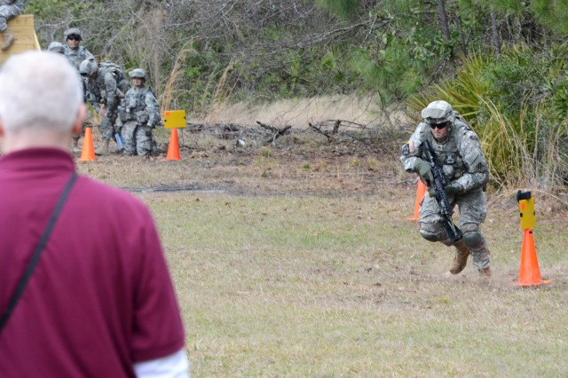 Sgt. Robon McKay dashes as if under enemy fire as an evaluator watches, during the Army Physical Demands Study, at Fort Stewart, Ga., March 12, 2014.