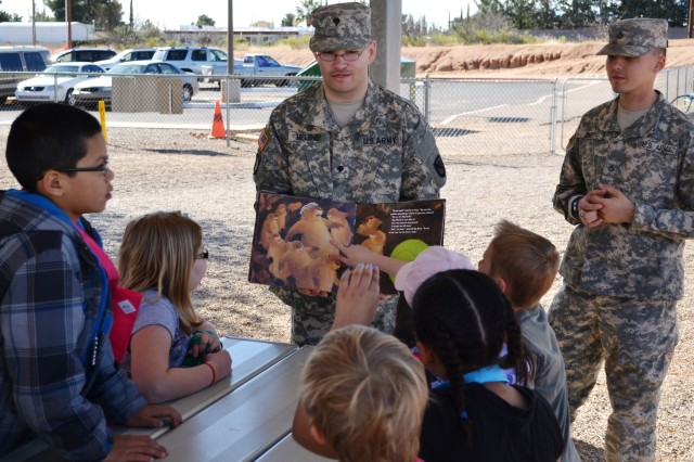 From left, Spc. Gerry Melendy and Pfc. David Casey from the Network Enterprise Technology Command, Fort Huachuca, read to children at the Town and Country Elementary School, Sierra Vista, during the school-wide Literacy Day, March 7. The Fort Huachuca Soldiers were among several organizations that participated in the event designed to encourage the students to read.