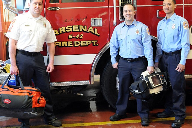 Daryle Wood (left), a fire inspector for the Rock Island Fire Department stands with Ryan McDonnell, firefighter/EMT, and Mark Abdon, firefighter/EMT, in the vehicle bay at RIA, March 7. (Photo by Sgt. 1st Class Shannon Wright, ASC Public Affairs)