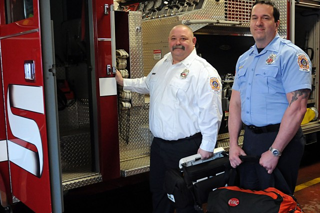 Capt. Tad Robison (left), a shift captain for the Rock Island Arsenal fire department stands next to John Pray, firefighter/EMT, in front of the truck engine in the vehicle bay at the RIA FD, March 7. (Photo by Sgt. 1st Class Shannon Wright, ASC Public Affairs)