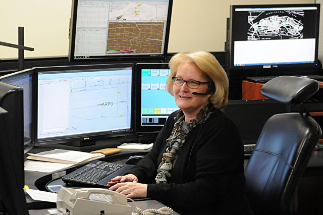 Rock Island Arsenal emergency dispatcher Terese Gleason responds to a call during her shift at the dispatch center March 7 at RIA. She and her co-workers dispatch for both the RIA fire department and the RIA police force. (Photo by Sgt. 1st Class Shannon Wright, ASC Public Affairs)