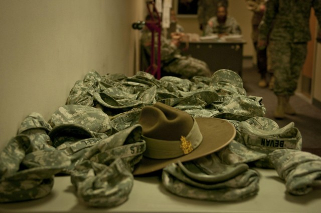 "An Australian Army ""slouch"" sits in a pile of U.S. Army patrol caps outside the security point for the 1st Cavalry Division's Command Post Exercise, March 15, 2014. No personal electronics are allowed in the high-security area of a joint operations center, so soldiers were putting their cell phones in their hats and placing them on the table before entering. (U.S. Army photo by Sgt. Ken Scar, 7th Mobile Public Affairs Detachment)"