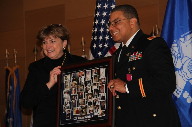 Jill Smith, CERDEC Director, gives Colonel Jacobs a framed poster with photos from his career at his retirement ceremony March 14 at Aberdeen Proving Ground, Md.