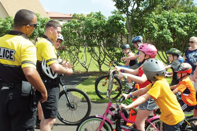 Spc. Thomas Loome (left, center), 13th MP Det., shares safety regulations with young bike riders at Wednesday�'s Bicycle Safety Bonanza.