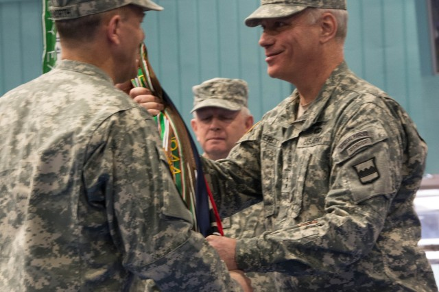 Col. Steven W. Ainsworth (L) assumes command of the 94th Training Division (FS) by accepting the command colors from Maj. Gen. Bill Gerety, commander 80th Training Command (TASS), during a Change of Command Ceremony at Fort Lee, Va., March 16, 2014. (background) outgoing commander Brig. Gen. Don S. Cornett, Jr. (Released) Photo by Cpt. Crystal Shamlee, 80th Training Command (TASS) public affairs