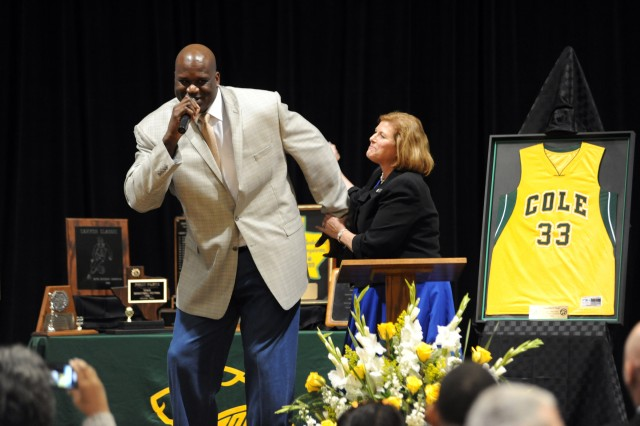 """Shaquille O'Neal hams it up on stage with Dr. Gail Siller, superintendent of the Fort Sam Houston Independent School District, during O'Neal's jersey retirement ceremony March 7, 2014, at Cole High School on Joint Base San Antonio-Fort Sam Houston, Texas. O'Neal, perhaps the world's largest self-professed Army brat, encouraged the students to live their dreams. April is Month of the Military Child and this year's theme is """"Young Lives, BIG Stories."""""""
