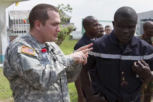 A U.S. Army soldier explains procedures of safely loading and unloading a rotary aircraft during Central Accord 14 at the 102 Air Force Base airfield in Douala Cameroon, March 13. The U.S. is working with Host Nation and Partner Nations in order to conduct familiarization in peacekeeping operations, humanitarian disaster response and combating terrorism for a stable and secure Africa.