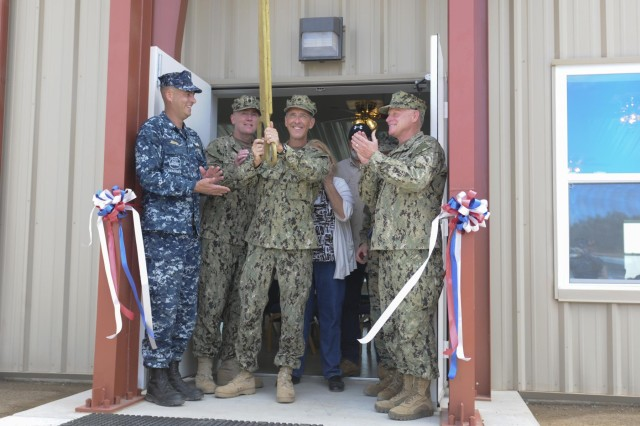 Cmdr. Terry Eddinger, Joint Task Force Chaplain cuts the ribbon to the new Trooper Chapel with Rear Admiral Richard Butler, (right) JTF Commander and other Troopers, Feb. 27 at JTF Guantanamo Bay, Cuba. This event celebrated the official opening of the long awaited, permanent chapel. (U.S. Army Photo by Pvt. Kourtney Grimes/ Released)